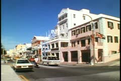 Front Street in Hamilton, Bermuda with traffic, motor scooters, and people Stock Footage