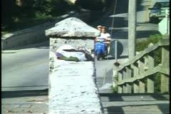 Moped, motor scooter, passing over bridge in Bermuda Stock Footage
