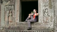 Stock Video Footage of caucasian tourist talking with mobile phone in angkor