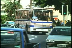City buses, blue and pink, Hamilton, Bermuda, in traffic Stock Footage