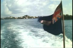 Stern of Ferry boat, no people, flag waving, choppy wash, Bermuda Stock Footage