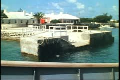POV from ferry boat passing a stone dock and house, Bermuda Stock Footage