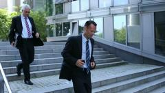 Business people running down stairs Stock Footage