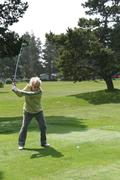 Woman golfer teeing off Stock Photos