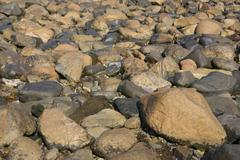 granite pebbles, rounded by the ocean - stock photo
