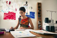 Hispanic woman doing budget in fashion designer atelier Stock Photos
