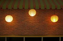 Brick wall with three illuminated lamps Stock Photos