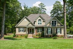 Upscale home on forested lot Stock Photos