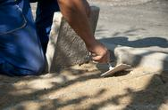 Stock Photo of worker puts sidewalk tiles