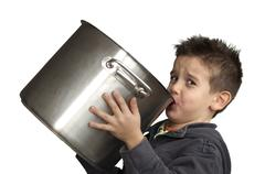 Child drinking milk from a big saucepan Stock Photos