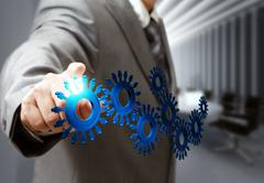 business man hand point cogs icons in board room - stock illustration