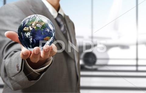"Stock Illustration of business man holds globe in the airport""elements of this image furnished by n"