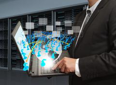 Stock Illustration of business man holds laptop computer and social network in server room