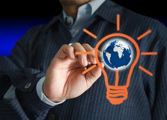 Stock Illustration of hand with a pen drawing light bulb and globe