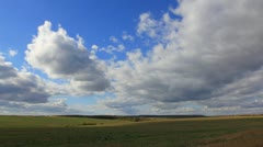 Large clouds flying on blue sky over autumn harvest field Stock Footage