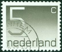 stamp printed in the Netherlands shows numeral ordinary gum, circa 1976. - stock photo