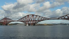 Yacht passing Forth Rail Bridge Scotland Stock Footage