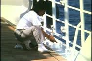 Man painting rails on a cruise ship, MV Horizon, Atlantic Ocean Stock Footage