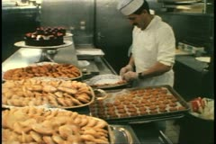Cruise ship galley, kitchen, MV Horizon, laying out deserts on trays Stock Footage