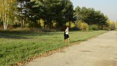 Businesswoman walking in autumn park with a cloak in the hands - stock footage
