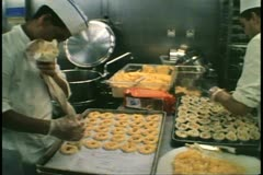 Squeezing out cookies from a pastry chef's bag, cruise ship galley, kitchen Stock Footage