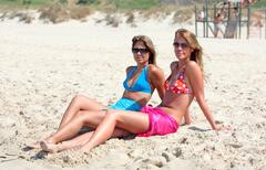 Two young attractive women chilling in the sun on holiday or vacation Stock Photos