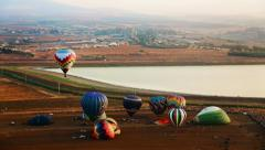 Hot air balloons take off at sunrise aerial timelapse Stock Footage