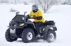 The quad bike driver rides over snow track Stock Photos