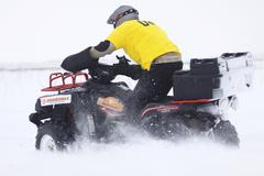 The quad bike driver rides over snow track - stock photo