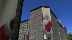 Banners of Santa Claus unfurl down buildings Stock Footage