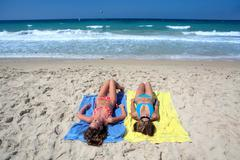 Two sexy young girls laying on a sunny beach on vacation or holiday Stock Photos