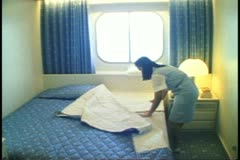 Young girl cabin stewardess makes bed in cabin on a cruise ship Stock Footage