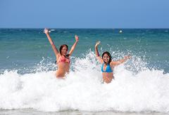 Two attractive young girl friends playing in the sea on vacation Stock Photos