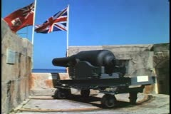 WWI canon, inside fort looking out, flags, St. Catherine's Fort, Bermuda Stock Footage