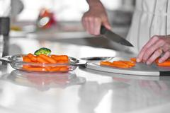 Carrot cutting in kitchen Stock Photos