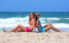 Two young sexy and healthy girls sitting on a sunny beach Stock Photos