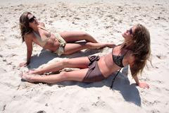 Two sexy young women sunbathing on a sandy beach - stock photo