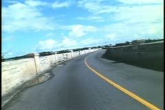 POV from moped, motor scooter, over long coral bridge in Bermuda Stock Footage
