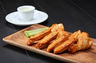 Stock Photo of Grilled chicken wings served on wooden board