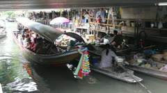 Tourist ride boat down canal Thailand floating market Stock Footage