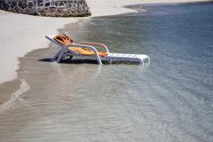 beach lounger in the water - stock photo