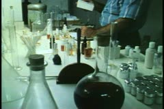 Perfumery laboratory in Bermuda, one man works with flasks and writes Stock Footage