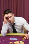 Worried man holding a cigar at poke at table - stock photo