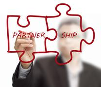 """Stock Illustration of businessman drawing """"partnership"""" written puzzle pieces"""