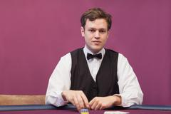 Stock Photo of Dealer sitting in a casino distributing chips