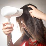 Woman with hair blow drier Stock Photos