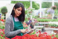 Employee checking flowers with tablet pc in garden center - stock photo