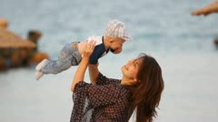 Young mother lifting up her baby at the seaside Stock Footage
