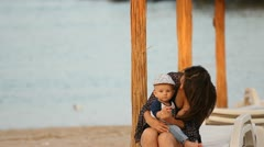 Little baby staying to his mother lap at the seaside Stock Footage