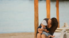 Mother talking to her baby at the seaside Stock Footage